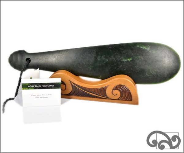Authentic greenstone mere on a wooden stand.