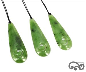 Greenstone pounamu drop carvings with koru